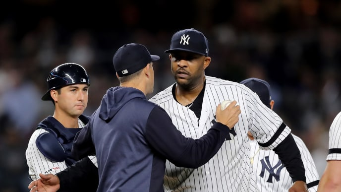 NEW YORK, NEW YORK - SEPTEMBER 18:  Manager Aaron Boone #17 of the New York Yankees hugs CC Sabathia #52 after he pulls him from the game in the third inning against the Los Angeles Angels at Yankee Stadium on September 18, 2019 in the Bronx borough of New York City. (Photo by Elsa/Getty Images)