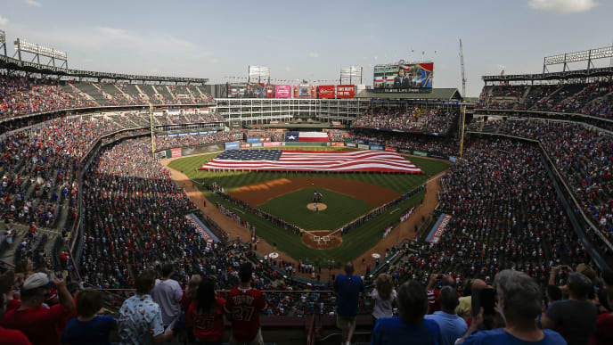 ARLINGTON, TX - JULY 4: Fans stand for the playing of the National Anthem before a baseball game between the Los Angeles Angels of Anaheim and Texas Rangers at Globe Life Park in Arlington on July 4, 2019 in Arlington, Texas. (Photo by Brandon Wade/Getty Images)
