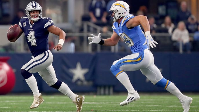 ARLINGTON, TX - NOVEMBER 23:  Dak Prescott #4 of the Dallas Cowboys scrambles under pressure from Joey Bosa #99 of the Los Angeles Chargers in the first quarter of a football game at AT&T Stadium on November 23, 2017 in Arlington, Texas.  (Photo by Tom Pennington/Getty Images)
