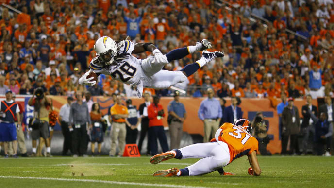 DENVER, CO - SEPTEMBER 11: Running back Melvin Gordon #28 of the Los Angeles Chargers dives over strong safety Justin Simmons #31 of the Denver Broncos in the second quarter at Sports Authority Field at Mile High on September 11, 2017 in Denver, Colorado. (Photo by Justin Edmonds/Getty Images)