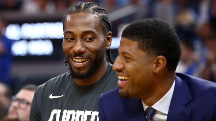 SAN FRANCISCO, CALIFORNIA - OCTOBER 24:   Kawhi Leonard #2 and Paul George #13 of the LA Clippers smile while sitting on the bench during their game against the Golden State Warriors at Chase Center on October 24, 2019 in San Francisco, California.  NOTE TO USER: User expressly acknowledges and agrees that, by downloading and or using this photograph, User is consenting to the terms and conditions of the Getty Images License Agreement. (Photo by Ezra Shaw/Getty Images)