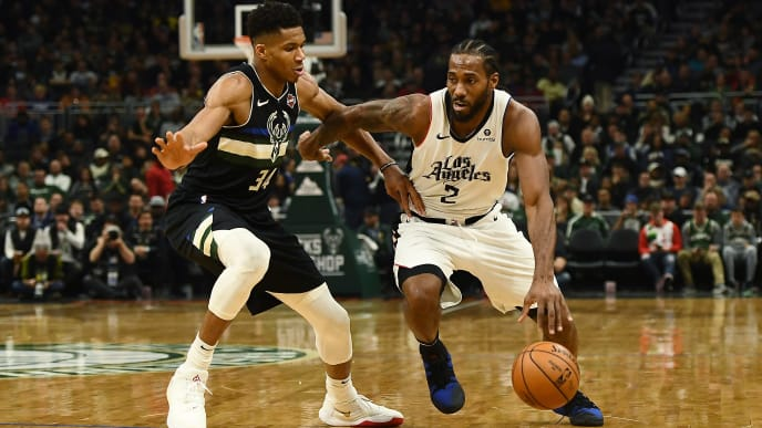 Kawhi Leonard dribbles defended by Giannis Antetokounmpo in recent game between Clippers and Bucks.