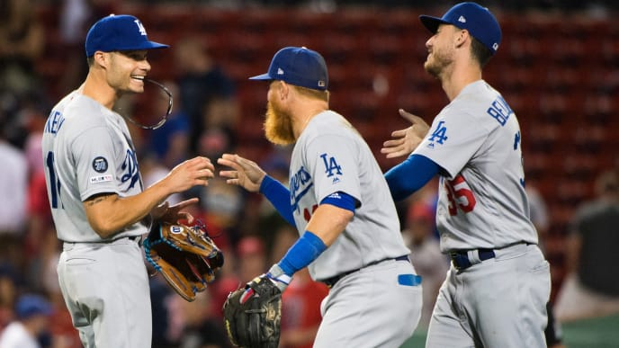 BOSTON, MA - JULY 15: Joe Kelly #17 celebrates with teammates Justin Turner #10 and Cody Bellinger #35 of the Los Angeles Dodgers after beating the Boston Red Sox in twelve innings at Fenway Park on July 15, 2019 in Boston, Massachusetts. (Photo by Kathryn Riley/Getty Images)