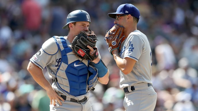 DENVER, COLORADO - JULY 31: Catcher Will Smith #16 and pitcher Joe Kelly #17 of the Los Angeles Dodgers confer in the eighth inning against the Colorado Rockies at Coors Field on July 31, 2019 in Denver, Colorado. (Photo by Matthew Stockman/Getty Images)