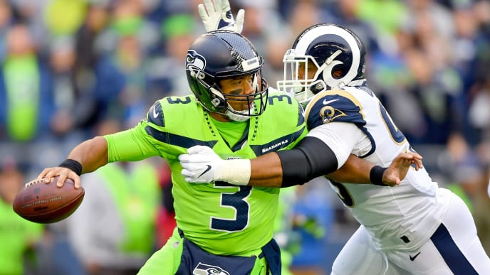SEATTLE, WASHINGTON - OCTOBER 03: Russell Wilson #3 of the Seattle Seahawks is pressured by Aaron Donald #99 of the Los Angeles Rams during the first half of the game at CenturyLink Field on October 03, 2019 in Seattle, Washington. (Photo by Alika Jenner/Getty Images)