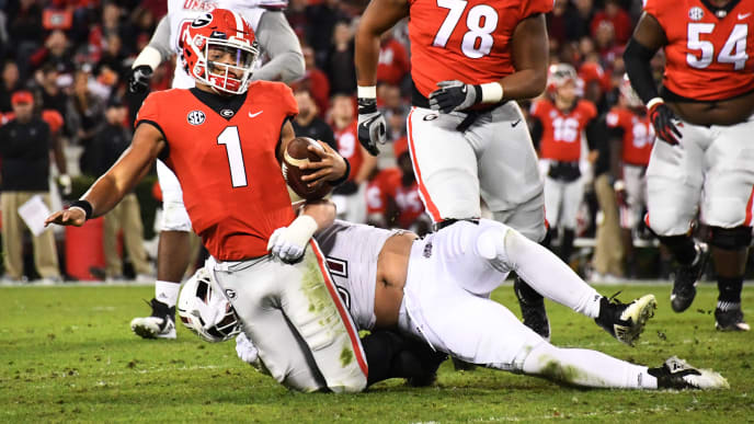 ATHENS, GA - NOVEMBER 17: Justin Fields #1 of the Georgia Bulldogs passes is tackled in the third quarter by Jake Byczko #97 of the Massachusetts Minutemen on November 17, 2018 at Sanford Stadium in Athens, Georgia. (Photo by Scott Cunningham/Getty Images)