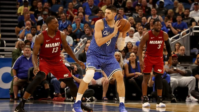 ORLANDO, FL - OCTOBER 17:  Nikola Vucevic #9 of the Orlando Magic looks to make a pass against Bam Adebayo #13 of the Miami Heat during the game at Amway Center on October 17, 2018 in Orlando, Florida.  NOTE TO USER: User expressly acknowledges and agrees that, by downloading and or using this photograph, User is consenting to the terms and conditions of the Getty Images License Agreement.  (Photo by Sam Greenwood/Getty Images)