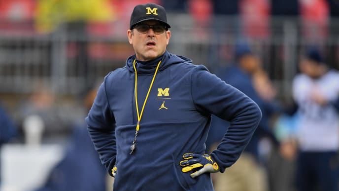 COLUMBUS, OH - NOVEMBER 24:  Head Coach Jim Harbaugh of the Michigan Wolverines watches his team warm up before a game against the Ohio State Buckeyes at Ohio Stadium on November 24, 2018 in Columbus, Ohio. Ohio State defeated Michigan 62-39.  (Photo by Jamie Sabau/Getty Images)