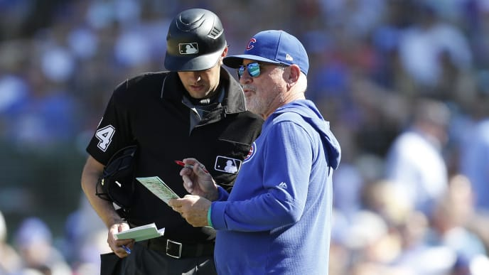 CHICAGO, ILLINOIS - AUGUST 02: Manager Joe Maddon #70 of the Chicago Cubs speaks with umpire John Tumpane #74 during the seventh inning of a game against the Milwaukee Brewers at Wrigley Field on August 02, 2019 in Chicago, Illinois. (Photo by Nuccio DiNuzzo/Getty Images)