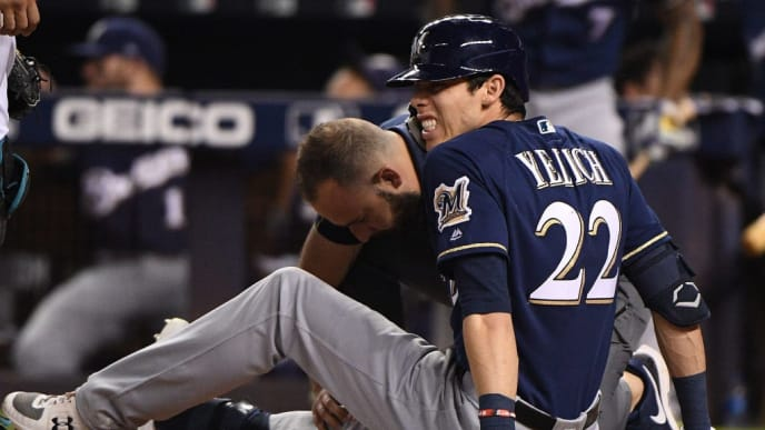 MIAMI, FLORIDA - SEPTEMBER 10: Christian Yelich #22 of the Milwaukee Brewers is checked out by the medical staff after an injury from ball deflection in the first inning against the Miami Marlins at Marlins Park on September 10, 2019 in Miami, Florida. (Photo by Mark Brown/Getty Images)
