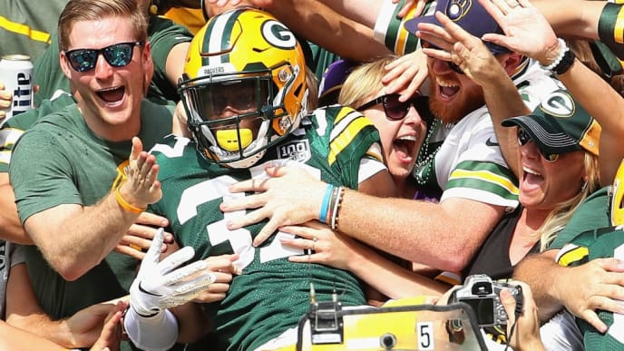 "GREEN BAY, WI - SEPTEMBER 16:  Josh Jackson #37 of the Green Bay Packers is grabbed by fans as he does  a ""Lambeau Leap"" after blocking a punt and scoring a touchdown against the Minnesota Vikings at Lambeau Field on September 16, 2018 in Green Bay, Wisconsin. The Vikings and the Packers tied 29-29 after overtime. (Photo by Jonathan Daniel/Getty Images)"