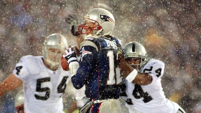 FOXBORO, UNITED STATES:  New England Patriots  quarterback Tom Brady (C) takes a hit from Charles Woodson (R) of the Oakland Raiders on a pass attempt in the last two minutes of the game in their AFC playoff 19 January 2002 in Foxboro, Massachusetts.  The Patriots won 16-13 in overtime. AFP PHOTO/Matt CAMPBELL (Photo credit should read MATT CAMPBELL/AFP via Getty Images)