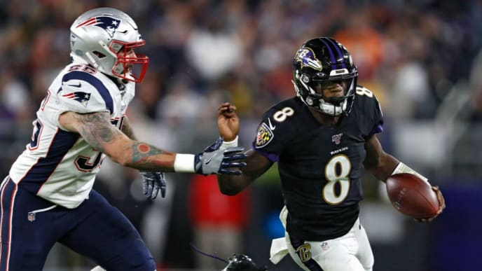 BALTIMORE, MARYLAND - NOVEMBER 03: Quarterback Lamar Jackson #8 of the Baltimore Ravens rushes past defensive end John Simon #55 of the New England Patriots during the first quarter at M&T Bank Stadium on November 3, 2019 in Baltimore, Maryland. (Photo by Scott Taetsch/Getty Images)