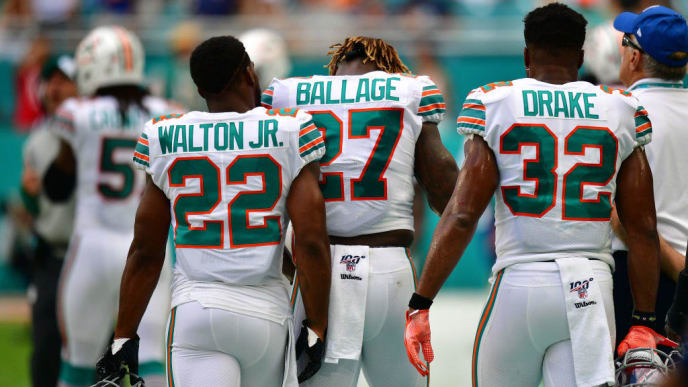 MIAMI, FLORIDA - SEPTEMBER 15: Mark Walton #22, Kalen Ballage #27 and Kenyan Drake #32 of the Miami Dolphins on the sidelines after an interception in the fourth quarter against the New England Patriots at Hard Rock Stadium on September 15, 2019 in Miami, Florida. (Photo by Mark Brown/Getty Images)