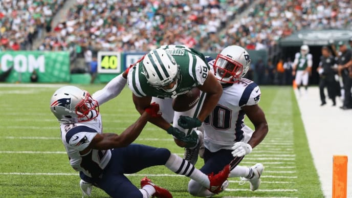 EAST RUTHERFORD, NJ - OCTOBER 15:  Tight end Austin Seferian-Jenkins #88 of the New York Jets is seen fumbling the ball after what was originally called a touchdown against strong safety Duron Harmon #30 and cornerback Malcolm Butler #21 of the New England Patriots during the fourth quarter of their game at MetLife Stadium on October 15, 2017 in East Rutherford, New Jersey. The Replay Official reviewed the runner broke the plane ruling, and the play was reversed and called a fumble.  (Photo by Al Bello/Getty Images)