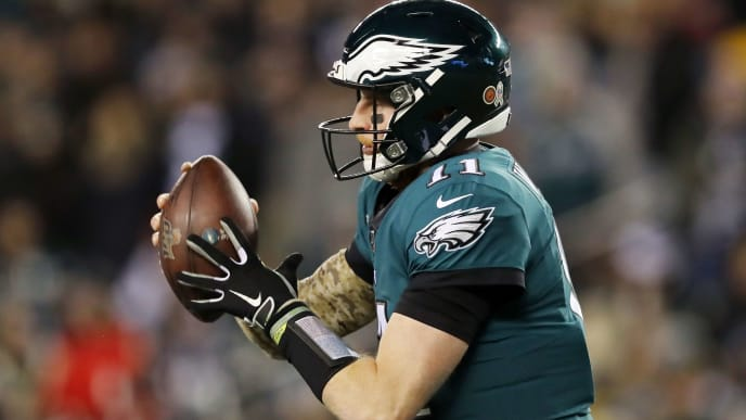PHILADELPHIA, PENNSYLVANIA - NOVEMBER 17:  Carson Wentz #11 of the Philadelphia Eagles handles the ball during the first half against the New England Patriots at Lincoln Financial Field on November 17, 2019 in Philadelphia, Pennsylvania. (Photo by Elsa/Getty Images)