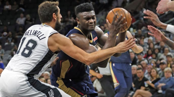 SAN ANTONIO,TX - OCTOBER 13: Zion Williamson #1  of the New Orleans Pelicans drives on Marco Belinelli #18 of the San Antonio Spurs in pre-season game  at AT&T Center on October 13 , 2019 in San Antonio, Texas.  NOTE TO USER: User expressly acknowledges and agrees that , by downloading and or using this photograph, User is consenting to the terms and conditions of the Getty Images License Agreement. (Photo by Ronald Cortes/Getty Images)