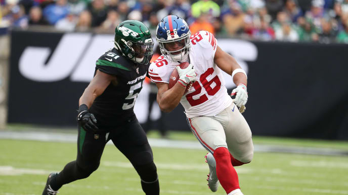 EAST RUTHERFORD, NEW JERSEY - NOVEMBER 10:  Saquon Barkley #26 of the New York Giants breaks a tackle against Brandon Copeland #51 of the New York Jets during their game at MetLife Stadium on November 10, 2019 in East Rutherford, New Jersey. (Photo by Al Bello/Getty Images)