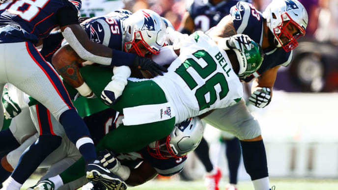 FOXBOROUGH, MA - SEPTEMBER 22: Le'Veon Bell #26 of the New York Jets is tackled by multiple New England Patriots during a game at Gillette Stadium on September 22, 2019 in Foxborough, Massachusetts.  (Photo by Adam Glanzman/Getty Images)