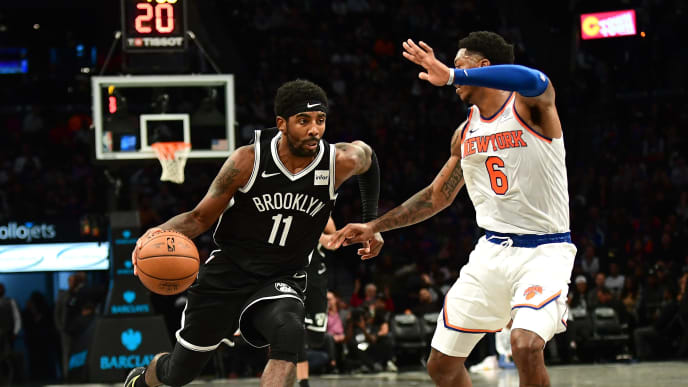 NEW YORK, NEW YORK - OCTOBER 25: Elfrid Payton #6 of the New York Knicks guards Kyrie Irving #11 of the Brooklyn Nets as he dribbles the ball in the first half of their game at Barclays Center on October 25, 2019 in the Brooklyn borough of New York City. NOTE TO USER: User expressly acknowledges and agrees that, by downloading and or using this photograph, User is consenting to the terms and conditions of the Getty Images License Agreement. (Photo by Emilee Chinn/Getty Images)