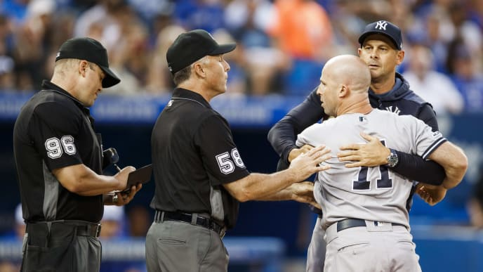TORONTO, ONTARIO - AUGUST 9: Brett Gardner #11 of the New York Yankees is held back by manager Aaron Boone as he argues with umpires while playing the Toronto Blue Jays  in the fourth inning during their MLB game at the Rogers Centre on August 9, 2019 in Toronto, Canada. (Photo by Mark Blinch/Getty Images)