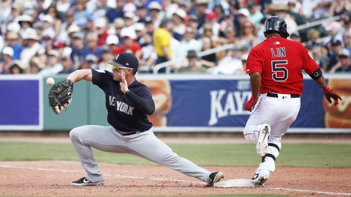 FORT MYERS, FL - FEBRUARY 23: Ryan McBroom #98 of the New York Yankees is unable to catch the ball as Tzu-Wei Lin #5 of the Boston Red Sox is safe at first base in the fifth inning of a Grapefruit League spring training game at JetBlue Park at Fenway South on February 23, 2019 in Fort Myers, Florida. The Red Sox won 8-5. (Photo by Joe Robbins/Getty Images)