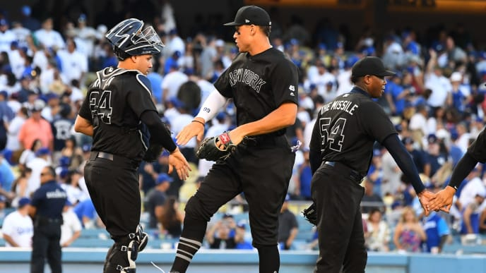 LOS ANGELES, CA - AUGUST 25: Aaron Judge #99 and Gary Sanchez #24 of the New York Yankees celebrate after the final out of the ninth inning defeating the Los Angeles Dodgers at Dodger Stadium on August 25, 2019 in Los Angeles, California. Teams are wearing special color schemed uniforms with players choosing nicknames to display for Players' Weekend. (Photo by Jayne Kamin-Oncea/Getty Images)