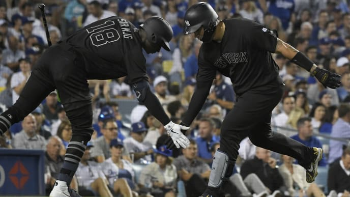 LOS ANGELES, CA - AUGUST 23: Didi Gregorius #18 of the New York Yankees congratulates Gary Sanchez #24 of the New York Yankees for his solo home run in the thrid inning against Hyun-Jin Ryu #99 of the Los Angeles Dodgers at Dodger Stadium on August 23, 2019 in Los Angeles, California. Teams are wearing special color schemed uniforms with players choosing nicknames to display for Players' Weekend. (Photo by John McCoy/Getty Images)