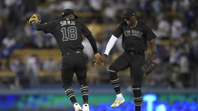 LOS ANGELES, CA - AUGUST 23: Didi Gregorius #18 of the New York Yankees leaps up to celebrate with Cameron Maybin #38 after defeating the Los Angeles Dodgers 10-2 at Dodger Stadium on August 23, 2019 in Los Angeles, California. Teams are wearing special color schemed uniforms with players choosing nicknames to display for Players' Weekend. (Photo by John McCoy/Getty Images)