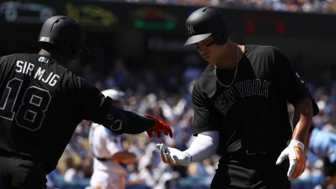LOS ANGELES, CALIFORNIA - AUGUST 24: Aaron Judge #99 of the New York Yankees celebrates with teammate Didi Gregorius #18 after Judge hit a solo home run during the fourth inning of the MLB game against the Los Angeles Dodgers at Dodger Stadium on August 24, 2019 in Los Angeles, California. Teams are wearing special color-schemed uniforms with players choosing nicknames to display for Players' Weekend. (Photo by Victor Decolongon/Getty Images)
