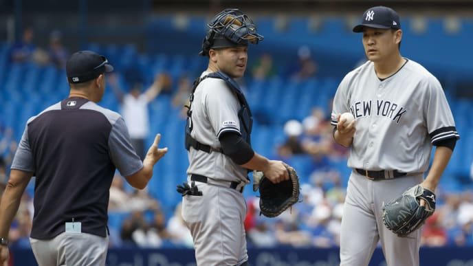 TORONTO, ON - AUGUST 11: Manager Aaron Boone #17 of the New York Yankees arrives at the mound with Austin Romine #28 as Masahiro Tanaka #19 is pulled from the game in the ninth inning of MLB action against the Toronto Blue Jays at Rogers Centre on August 11, 2019 in Toronto, Canada. (Photo by Cole Burston/Getty Images)