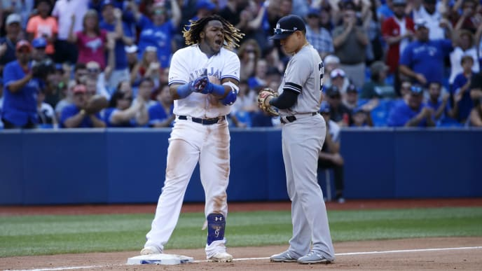 TORONTO, ON - AUGUST 10: Vladimir Guerrero Jr. #27 of the Toronto Blue Jays reacts as he is held at third base by Gio Urshela #29 of the New York Yankees after hitting a triple, allowing 2 runs in the 7th inning during MLB action against the New York Yankees at Rogers Centre on August 10, 2019 in Toronto, Canada. (Photo by Cole Burston/Getty Images)