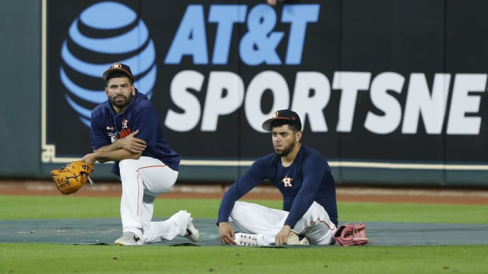 HOUSTON, TEXAS - JULY 22: Jose Urquidy #65 of the Houston Astros, left, and Roberto Osuna #54 sit in the outfield during batting practice before a baseball game with the Oakland Athletics at Minute Maid Park on July 22, 2019 in Houston, Texas. (Photo by Bob Levey/Getty Images)
