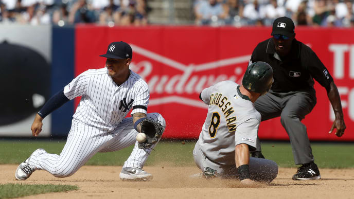 NEW YORK, NEW YORK - AUGUST 31:   Robbie Grossman #8 of the Oakland Athletics steals second base in the seventh inning ahead of the tag from Gleyber Torres #25 of the New York Yankees  at Yankee Stadium on August 31, 2019 in New York City. (Photo by Jim McIsaac/Getty Images)