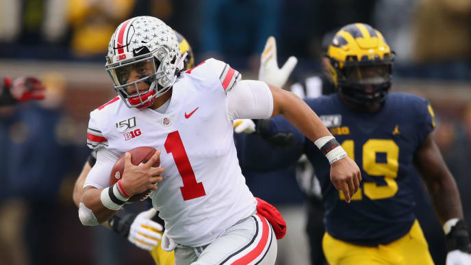 ANN ARBOR, MICHIGAN - NOVEMBER 30: Justin Fields #1 of the Ohio State Buckeyes looks for yards during a second quarter run in front of Kwity Paye #19 of the Michigan Wolverines at Michigan Stadium on November 30, 2019 in Ann Arbor, Michigan. (Photo by Gregory Shamus/Getty Images)