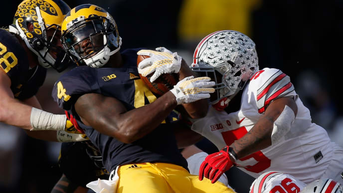 ANN ARBOR, MI - NOVEMBER 28: Running back De'Veon Smith #4 of the Michigan Wolverines is tackled by Raekwon McMillan #5 of the Ohio State Buckeyes in the fourth quarter at Michigan Stadium on November 28, 2015 in Ann Arbor, Michigan.  (Photo by Gregory Shamus/Getty Images)