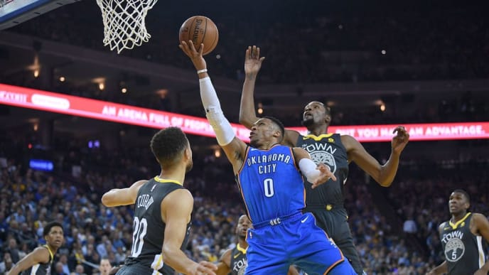 OAKLAND, CA - FEBRUARY 06:  Russell Westbrook #0 of the Oklahoma City Thunder goes up for a layup in front of Kevin Durant #35 of the Golden State Warriors and gets fouled by Stephen Curry #30 during the first half of their NBA basketball game at ORACLE Arena on February 6, 2018 in Oakland, California. NOTE TO USER: User expressly acknowledges and agrees that, by downloading and or using this photograph, User is consenting to the terms and conditions of the Getty Images License Agreement.  (Photo by Thearon W. Henderson/Getty Images)