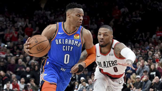 PORTLAND, OR - APRIL 14:  Russell Westbrook #0 of the Oklahoma City Thunder drives to the basket on Damian Lillard #0 of the Portland Trail Blazers during the second half of the game at the Moda Center on April 14, 2019 in Portland, Oregon. The Blazers won 104-99. NOTE TO USER: User expressly acknowledges and agrees that, by downloading and or using this photograph, User is consenting to the terms and conditions of the Getty Images License Agreement. (Photo by Steve Dykes/Getty Images)