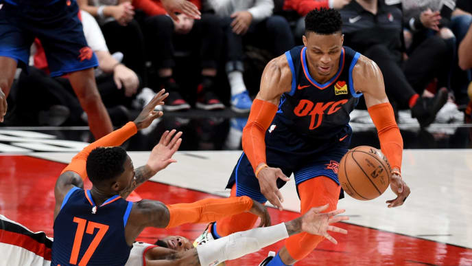 PORTLAND, OREGON - APRIL 23: Damian Lillard #0 of the Portland Trail Blazers sprawls on the court as Dennis Schroder #17 and Russell Westbrook #0 of the Oklahoma City Thunder go after a ball during the second half of Game Five of the Western Conference quarterfinals during the 2019 NBA Playoffs at Moda Center on April 23, 2019 in Portland, Oregon. The Blazers won 118-115.  NOTE TO USER: User expressly acknowledges and agrees that, by downloading and or using this photograph, User is consenting to the terms and conditions of the Getty Images License Agreement. (Photo by Steve Dykes/Getty Images)