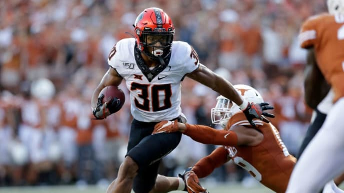 AUSTIN, TX - SEPTEMBER 21:  Chuba Hubbard #30 of the Oklahoma State Cowboys breaks a tackle by Ta'Quon Graham #49 of the Texas Longhorns in the first quarter at Darrell K Royal-Texas Memorial Stadium on September 21, 2019 in Austin, Texas.  (Photo by Tim Warner/Getty Images)
