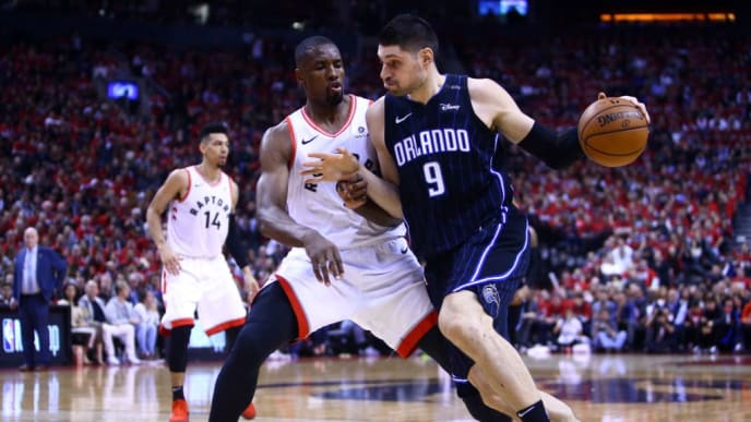 TORONTO, ON - APRIL 13:  Nikola Vucevic #9 of the Orlando Magic dribbles the ball as Serge Ibaka #9 of the Toronto Raptors defends during Game One of the first round of the 2019 NBA playoffs at Scotiabank Arena on April 13, 2019 in Toronto, Canada.  NOTE TO USER: User expressly acknowledges and agrees that, by downloading and or using this photograph, User is consenting to the terms and conditions of the Getty Images License Agreement.  (Photo by Vaughn Ridley/Getty Images)