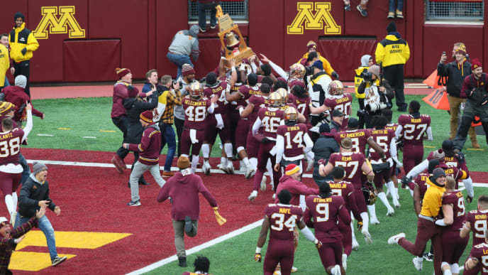MINNEAPOLIS, MN - NOVEMBER 09: Minnesota Golden Gophers and fans take the field while hoisting the Governor's Victory Bell after defeating the Penn State Nittany Lions 31-26 to remain undefeated at TCFBank Stadium on November 9, 2019 in Minneapolis, Minnesota. (Photo by Adam Bettcher/Getty Images)