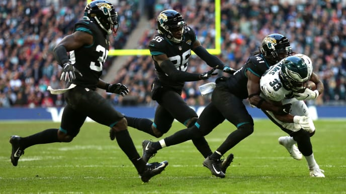LONDON, ENGLAND - OCTOBER 28: Josh Adams of The Eagles is chased by (L-R) Chandon Sullivan, Ronnie Harrison and Tre Herndon of The Jaguars during the NFL International Series match between Philadelphia Eagles and Jacksonville Jaguars at Wembley Stadium on October 28, 2018 in London, England. (Photo by Kate McShane/Getty Images)