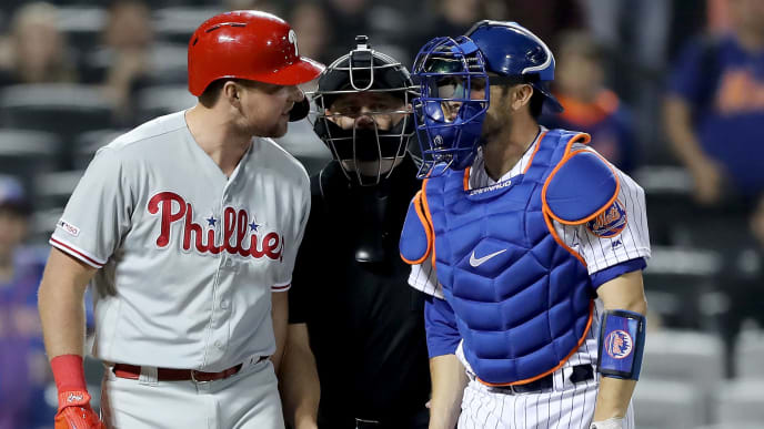 NEW YORK, NEW YORK - APRIL 23:  Rhys Hoskins #17 of the Philadelphia Phillies and Travis d'Arnaud #18 of the New York Mets have words as they are separated by home plate umpire Scott Barry in the ninth inning at Citi Field on April 23, 2019 in the Flushing neighborhood of the Queens borough of New York City.The New York Mets defeated the Philadelphia Phillies 9-0. (Photo by Elsa/Getty Images)