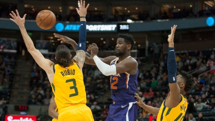 SALT LAKE CITY, UT -  FEBRUARY 6: Deandre Ayton #22  of the Phoenix Suns passes off under the basket while being guarded by Ricky Rubio #3 and Donovan Mitchell #45 of the Utah Jazz during a game at the Vivint Smart Home Arena on February 6, 2019 in Salt Lake City , Utah. NOTE TO USER: User expressly acknowledges and agrees that, by downloading and or using this photograph, User is consenting to the terms and conditions of the Getty Images License Agreement.(Photo by Chris Gardner/Getty Images)