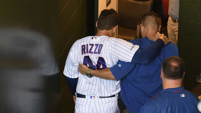 CHICAGO, ILLINOIS - SEPTEMBER 15: Anthony Rizzo #44 of the Chicago Cubs is helped in the dugout by trainer PJ Mainville after being injured against the Pittsburgh Pirates during the third inning at Wrigley Field on September 15, 2019 in Chicago, Illinois. (Photo by David Banks/Getty Images)