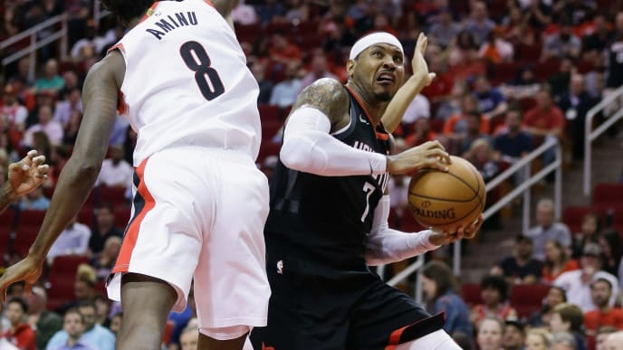 HOUSTON, TX - OCTOBER 30:  Carmelo Anthony #7 of the Houston Rockets shoots between Al-Farouq Aminu #8 of the Portland Trail Blazers and Evan Turner #1 during the fourth quarter at Toyota Center on October 30, 2018 in Houston, Texas. NOTE TO USER: User expressly acknowledges and agrees that, by downloading and or using this photograph, User is consenting to the terms and conditions of the Getty Images License Agreement.  (Photo by Bob Levey/Getty Images)