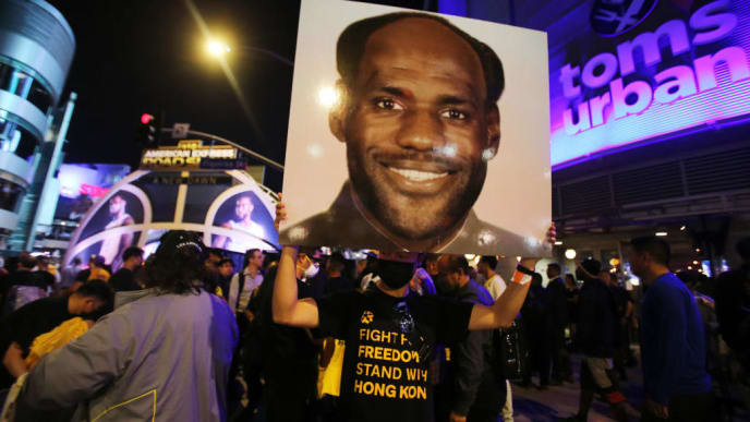 LOS ANGELES, CALIFORNIA - OCTOBER 22: A pro-Hong Kong activist holds an image depicting LeBron James as Chinese communist revolutionary Chairman Mao Zedong before the Los Angeles Lakers season opening game against the against the LA Clippers, outside Staples Center, on October 22, 2019 in Los Angeles, California. Activists also printed at least 10,000 pro-Hong Kong t-shirts to hand out to those attending the game and encouraged them to wear the free shirts as a form of peaceful protest against China amidst Chinese censorship of NBA games.  (Photo by Mario Tama/Getty Images)