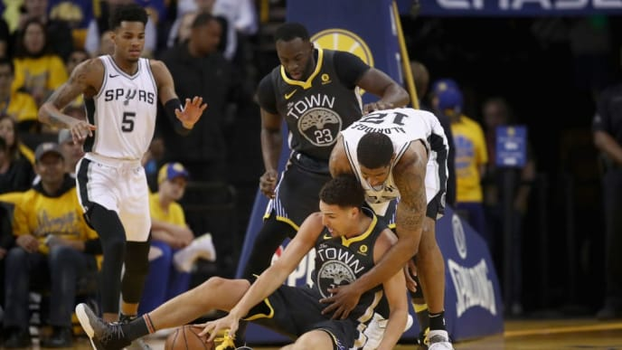 OAKLAND, CA - APRIL 16:  Klay Thompson #11 of the Golden State Warriors and LaMarcus Aldridge #12 of the San Antonio Spurs go for a loose ball during Game 2 of Round 1 of the 2018 NBA Playoffs at ORACLE Arena on April 16, 2018 in Oakland, California. NOTE TO USER: User expressly acknowledges and agrees that, by downloading and or using this photograph, User is consenting to the terms and conditions of the Getty Images License Agreement.  (Photo by Ezra Shaw/Getty Images)