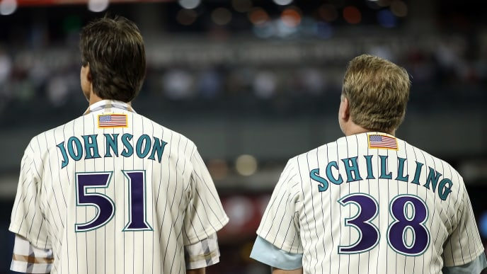 PHOENIX, AZ - SEPTEMBER 10:  Randy Johnson and Curt Schilling, former members of the 2001 Arizona Diamondbacks World Series team stand attended for the National Anthem before the Major League Baseball game against the San Diego Padres at Chase Field on September 10, 2011 in Phoenix, Arizona. The Diamondbacks are celebrating the 10th anniversary of their World Series title.  (Photo by Christian Petersen/Getty Images)